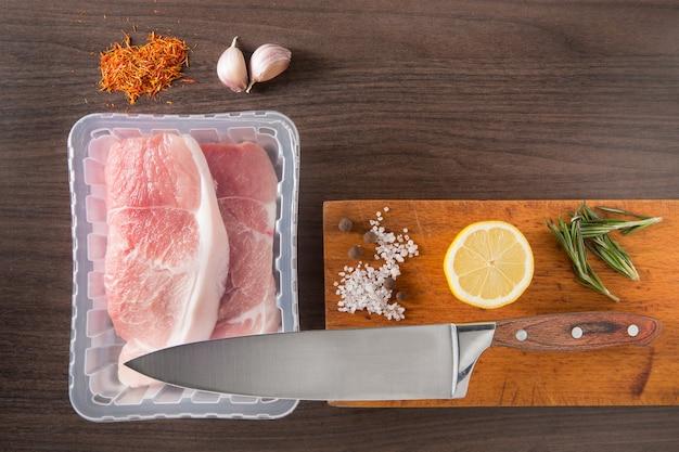 Widok z góry świeże pakowane surowe mięso na starej drewnianej desce do krojenia z nożem z wolnego miejsca na tekst.