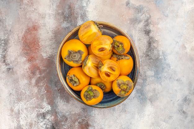 Widok z góry świeże persimmons w okrągłym drewnianym pudełku na nagim tle