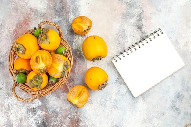 Widok z góry świeże persimmons w wiklinowym koszu tpersimmons notatnik na nagim tle