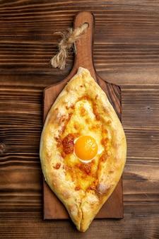 Widok z góry świeże pieczone pieczywo z gotowanym jajkiem na drewnianej powierzchni chleb ciasto bułka śniadanie żywności