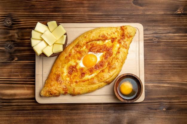 Widok z góry świeże pieczone pieczywo z gotowanym jajkiem na drewnianym biurku ciasto mąka bułka śniadanie jajka żywność
