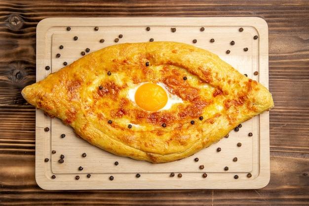 Widok z góry świeże pieczywo z gotowanym jajkiem na brązowym rustykalnym cieście śniadanie jajko bułka jedzenie