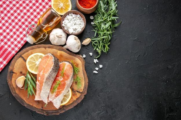 Widok z góry świeże plastry ryb z plasterkami cytryny czosnkiem i przyprawami na ciemnym stole