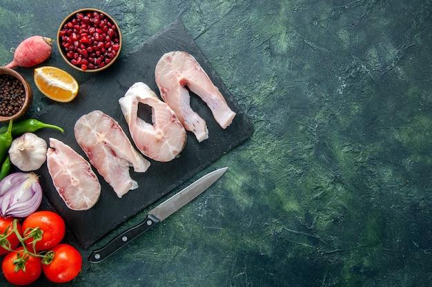 Widok z góry świeże plastry ryby z czerwonymi pomidorami na ciemnoniebieskim tle ocean mięso owoce morza pieprz danie jedzenie posiłek morski woda