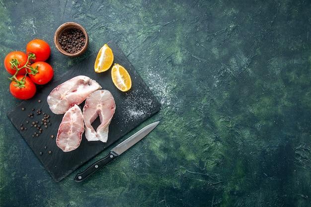 Widok z góry świeże plastry ryby z czerwonymi pomidorami na ciemnoniebieskim tle ocean mięso owoce morza posiłek morski danie jedzenie pieprz woda wolna przestrzeń
