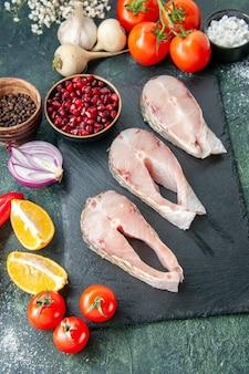Widok z góry świeże plastry ryby z czerwonymi pomidorami na ciemnym stole owoce morza mięso oceanu mączka morska pieprz danie jedzenie sałatka woda