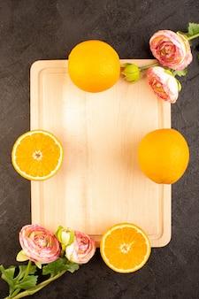 Widok z góry świeże pomarańcze kwaśne dojrzałe w całości z suszonych róż łagodny cytrus tropikalny tropikalny witaminowy żółty na ciemnym biurku