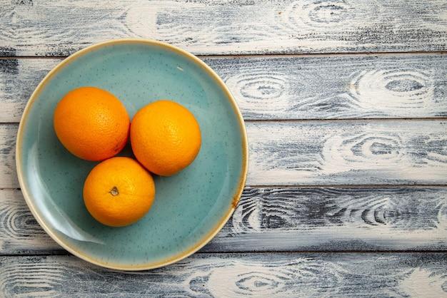 Widok z góry świeże pomarańcze wewnątrz na szaro-rustykalnej powierzchni