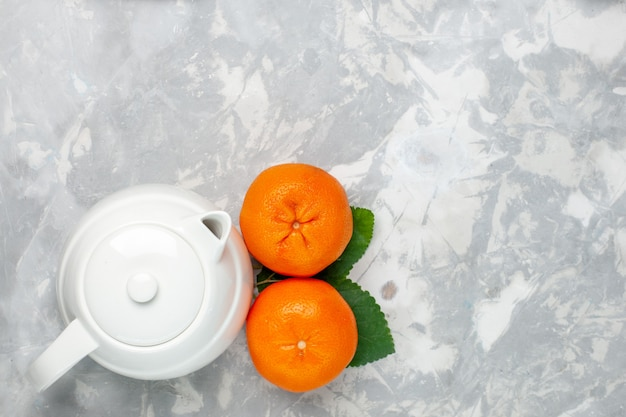 Widok z góry świeże pomarańcze z czajnikiem na jasnobiałym tle owoce cytrusowe świeże egzotyczne tropikalne
