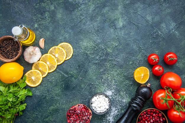Widok z góry świeże pomidory butelka oleju młynek do pieprzu plasterki cytryny na stole kuchennym z miejscem na kopię