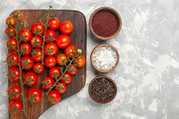 Widok z góry świeże pomidory czereśniowe dojrzałe całe warzywa z przyprawami na białej powierzchni