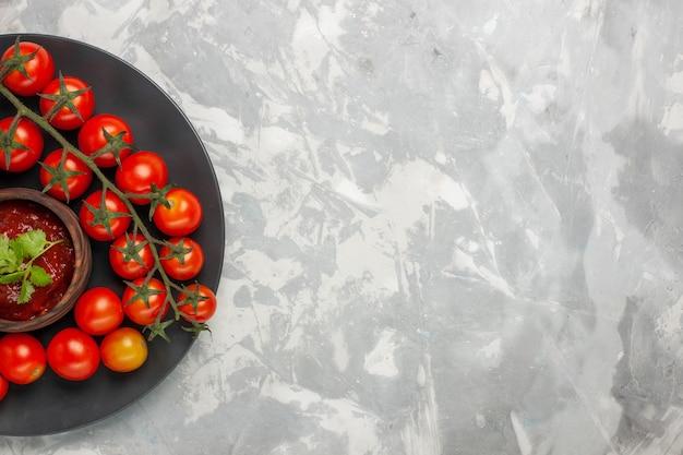 Widok z góry świeże pomidory czereśniowe wewnątrz płyty na białym biurku