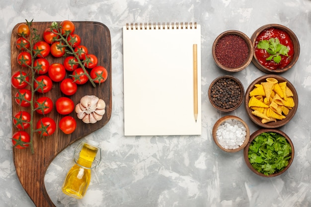 Widok z góry świeże pomidory koktajlowe z przyprawami i notatnikiem na białej powierzchni