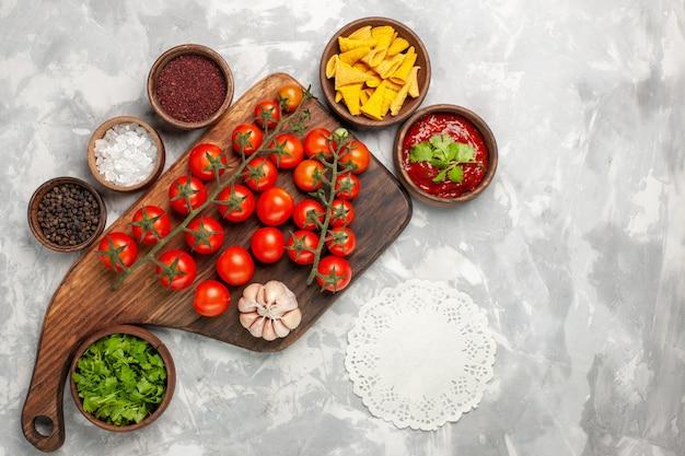 Widok z góry świeże pomidory koktajlowe z przyprawami i zieleniną na białej powierzchni