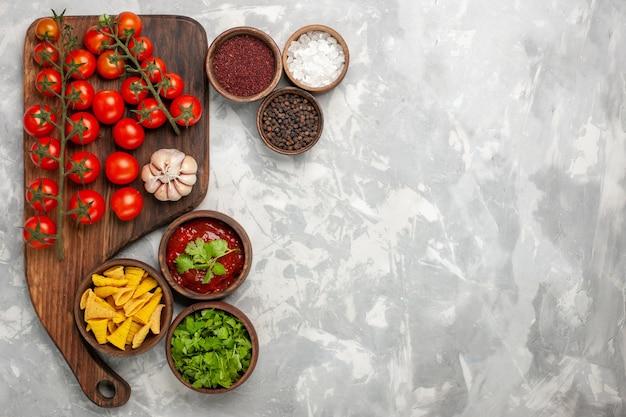 Widok z góry świeże pomidory koktajlowe z przyprawami na jasnobiałej powierzchni