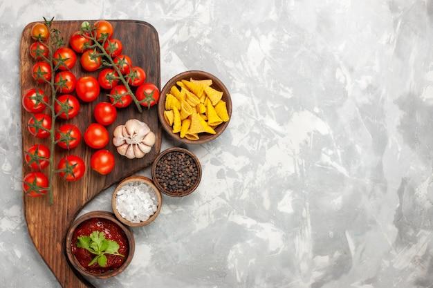 Widok z góry świeże pomidory koktajlowe z różnymi przyprawami na białej powierzchni