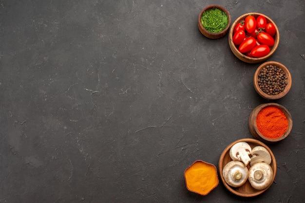 Widok z góry świeże pomidory z przyprawami i grzybami na ciemnej powierzchni dojrzałej sałatki w kolorze żywności