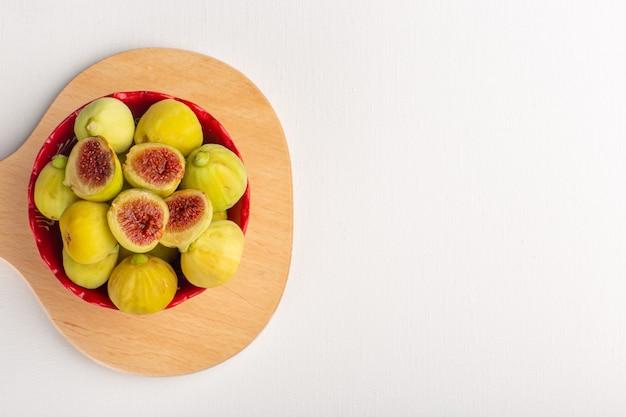 Widok z góry świeże słodkie figi pyszne płody wewnątrz czerwonego talerza na białym biurku