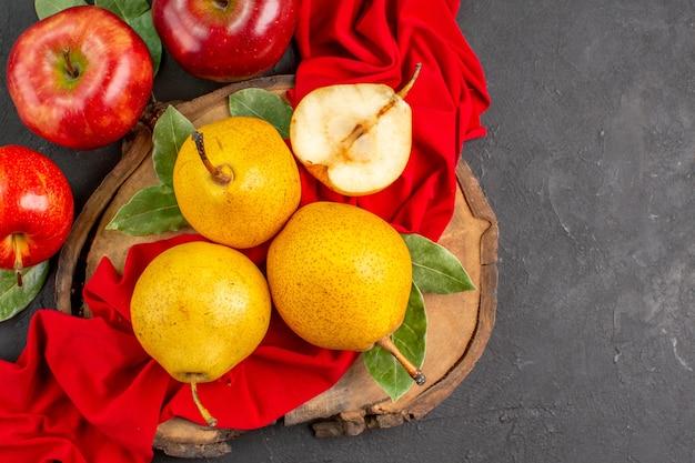 Widok z góry świeże słodkie gruszki z jabłkami na ciemnym stole świeży kolor dojrzały aksamitny