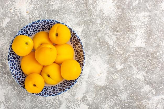Widok z góry świeże słodkie morele żółte owoce wewnątrz płyty na białej powierzchni