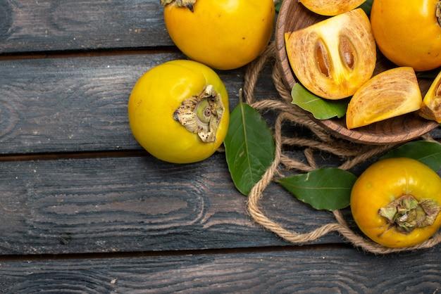 Widok z góry świeże słodkie persymony na drewnianej rustykalnej podłodze smakują dojrzałe owoce