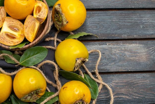 Widok z góry świeże słodkie persymony na drewnianym stole w stylu rustykalnym, dojrzałe owoce