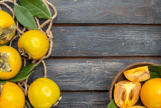 Widok z góry świeże słodkie persymony na drewnianym stole w stylu rustykalnym, smak dojrzałych owoców