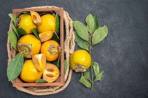 Widok z góry świeże słodkie persymony wewnątrz pudełka na ciemnym stole o smaku owoców dojrzałych
