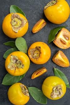 Widok z góry świeże słodkie persymony z liśćmi na ciemnym stole smakują owoce