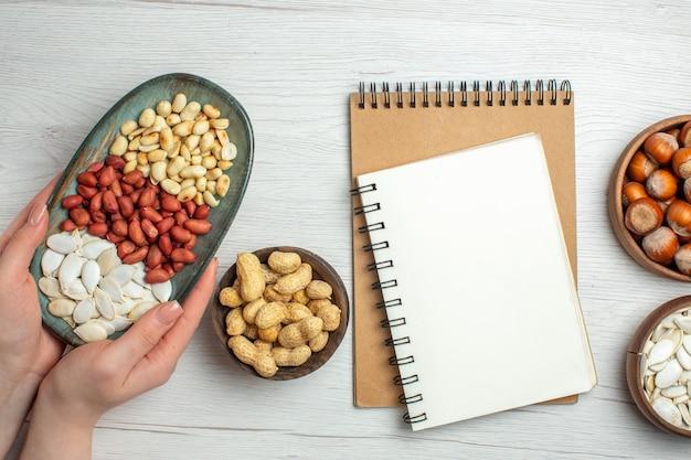 Widok z góry świeże smaczne orzeszki ziemne z białymi nasionami i orzechami laskowymi na białym stole