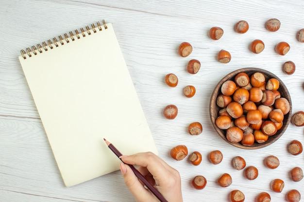 Widok z góry świeże surowe orzechy laskowe na białym biurku nakrętka przekąska filmy roślina jedzenie orzech włoski