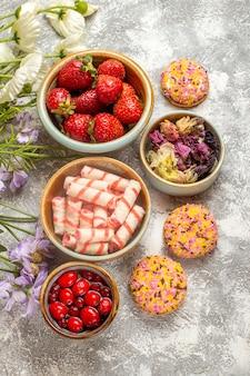 Widok z góry świeże truskawki z cukierkami i ciasteczkami na lekkiej powierzchni biszkopt owocowy słodki