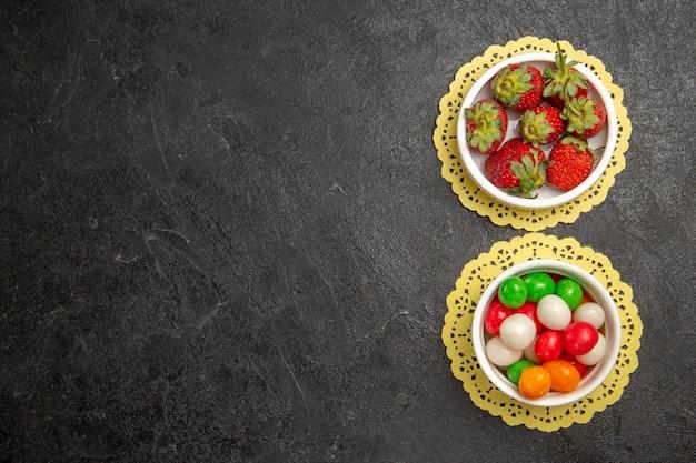 Widok z góry świeże truskawki z kolorowymi cukierkami na ciemnym tle owocowe jagody kolor tęczowy cukierek