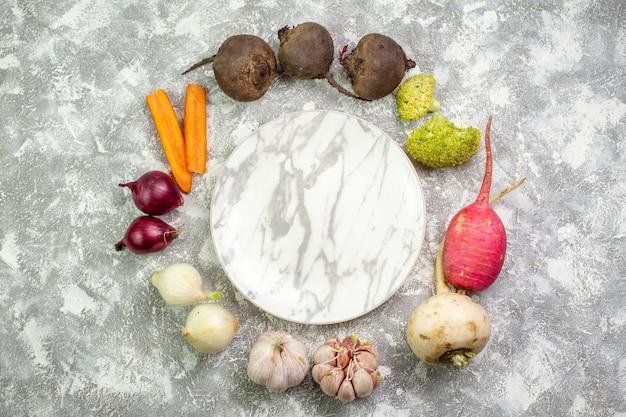 Widok z góry świeże warzywa burak rzodkiewka czosnek i cebula na białym biurku