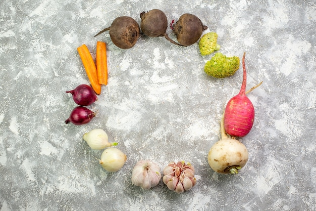Widok z góry świeże warzywa burak rzodkiewka czosnek i cebula na białym stole