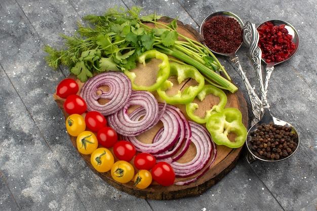 Widok z góry świeże warzywa pokrojone i całe, takie jak żółte czerwone pomidory i cebula na brązowym biurku na szaro