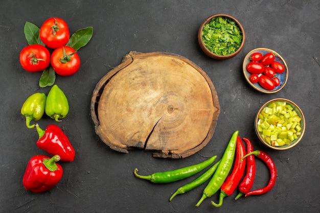 Widok z góry świeże warzywa pomidory i papryka na ciemnym stole, kolor dojrzałego posiłku sałatka