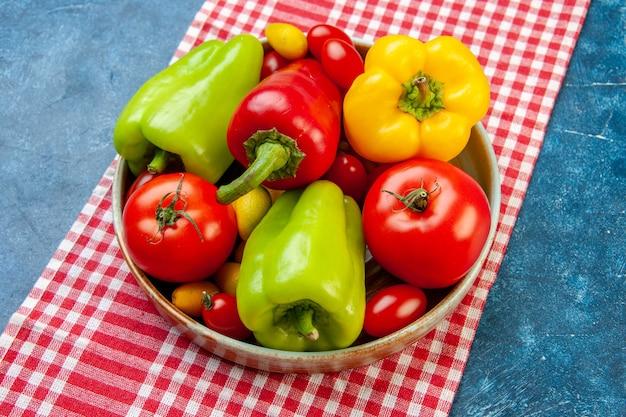 Widok z góry świeże warzywa pomidory koktajlowe różne kolory papryka pomidory cumcuat na talerzu na czerwonym i białym obrusie w kratkę na niebieskim stole