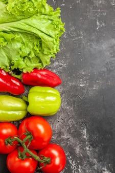 Widok z góry świeże warzywa pomidory zielona i czerwona papryka sałata na ciemnej powierzchni wolne miejsce