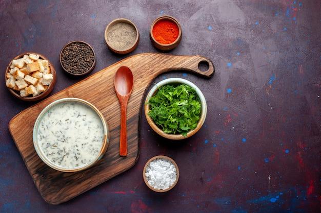 Widok z góry świeże warzywa wewnątrz okrągłej miski z gołębiem i sucharkami na ciemnym stole, zielone świeże warzywa spożywcze