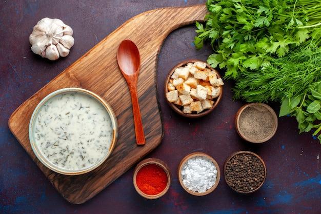 Widok z góry świeże warzywa wewnątrz okrągłej miski z przyprawami dovga i sucharkami na ciemnym stole, zielone świeże warzywa spożywcze