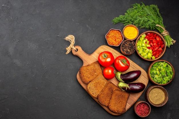 Widok z góry świeże warzywa z ciemnymi bochenkami chleba i przyprawami na ciemnej powierzchni sałatka posiłek chleb jedzenie