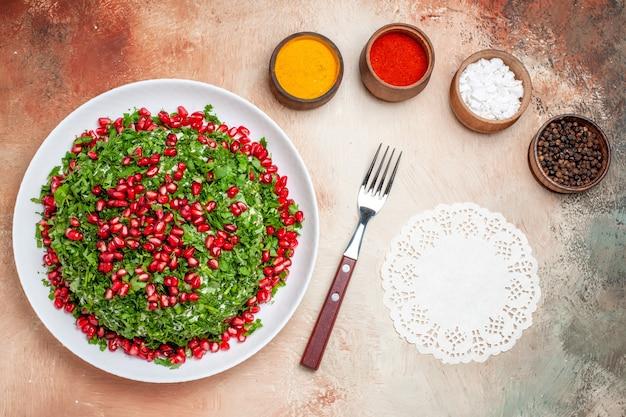 Widok z góry świeże warzywa z granatami i przyprawami na jasnym stole z zielonym posiłkiem owocowym