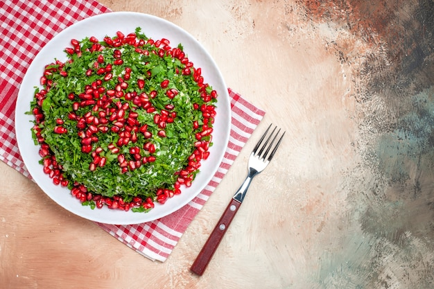 Widok z góry świeże warzywa z obranymi granatami na jasnym stole owoce zielony posiłek