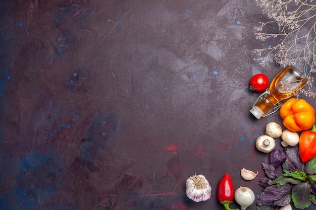 Widok z góry świeże warzywa z olejem na ciemnej powierzchni sałatka zdrowa żywność posiłek