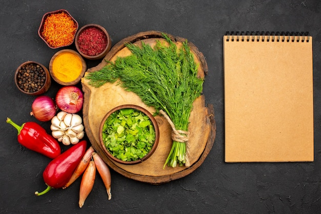 Widok z góry świeże warzywa z przyprawami i zieleniną na ciemnej powierzchni sałatka zdrowie dojrzały posiłek warzywny