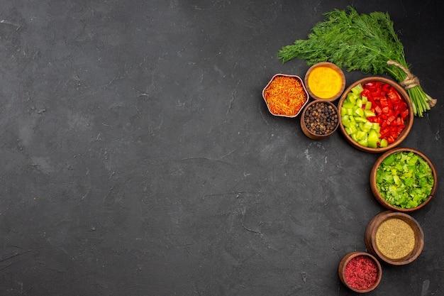 Widok z góry świeże warzywa z przyprawami na ciemnej powierzchni sałatka posiłek chleb jedzenie