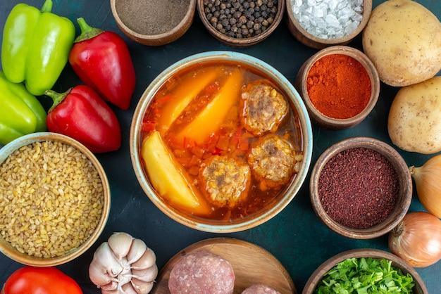 Widok z góry świeże warzywa z przyprawami zupa mięsna i zielenina na ciemnoniebieskiej powierzchni