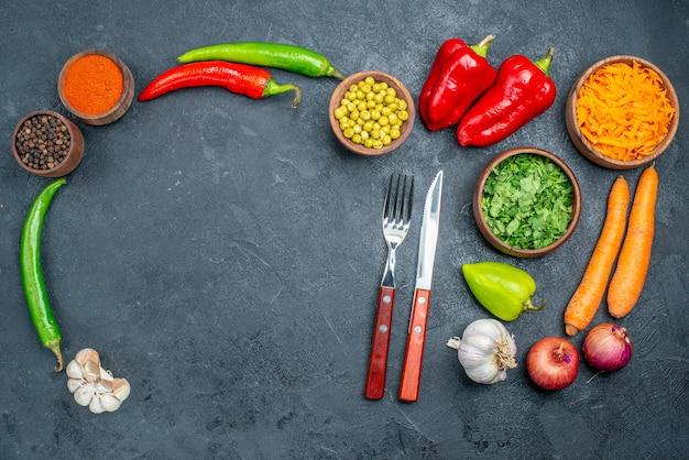 Widok z góry świeże warzywa z zielenią na ciemnym stole dojrzałe sałatki warzywne