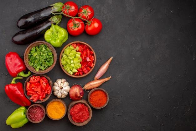 Widok z góry świeże warzywa z zieleniną i różnymi przyprawami na szarej sałatce na biurko sałatka ze zdrowej żywności
